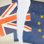 Image of a family snap photo showing the United Kingdom Union Jack and European Community flags - ripped in two as a divorce photo.