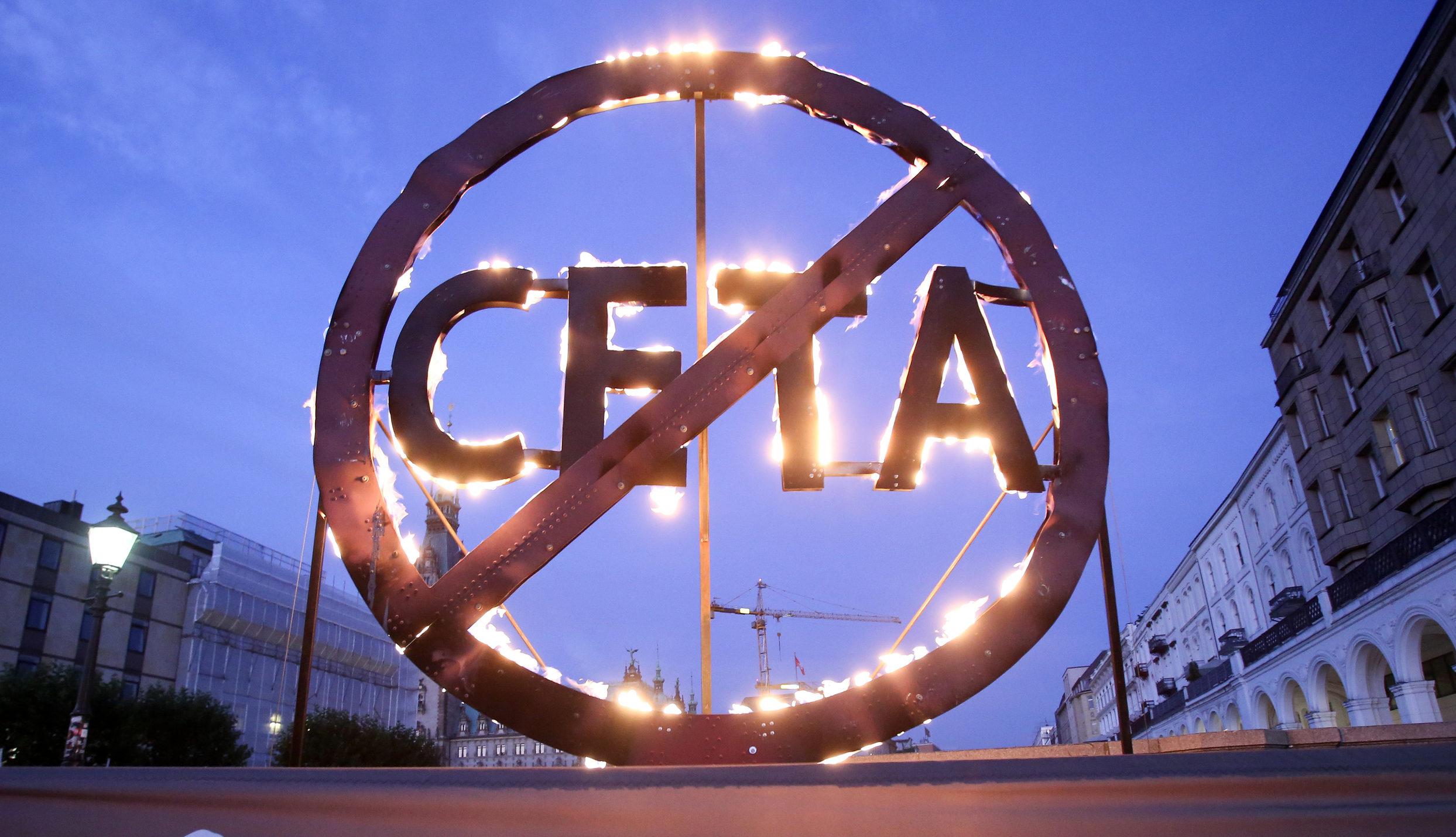 """Greenpeace activists demonstrate for more resistance against the Canadian European Trade Agreement (CETA) with a burning CETA sign in front of the Parliament in Hamburg. Fuer mehr Widerstand gegen das hochumstrittene kanadisch-europaeische Handelsabkommen CETA demonstrieren Greenpeace-Aktivisten am fruehen Morgen vor dem Landesparlament in Hamburg. Mit einem drei Meter großen, gluehenden CETA-Symbol und einem Banner warnen die Umweltschuetzer:""""CETA ist brandgefaehrlich""""."""